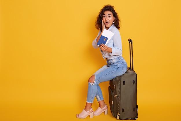 Взволнованная и счастливая молодая жизнерадостная женщина-турист сидит на своем большом чемодане