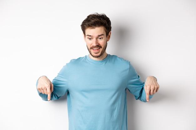 興奮して幸せな若い男は、素晴らしい取引を見て、下向きに、プロモーションのオファーをチェックして、白い背景の上に立っています