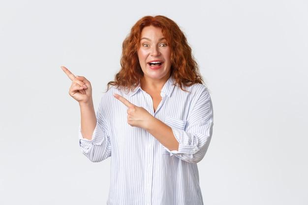 Возбужденная и впечатленная рыжая женщина средних лет показывает объявление