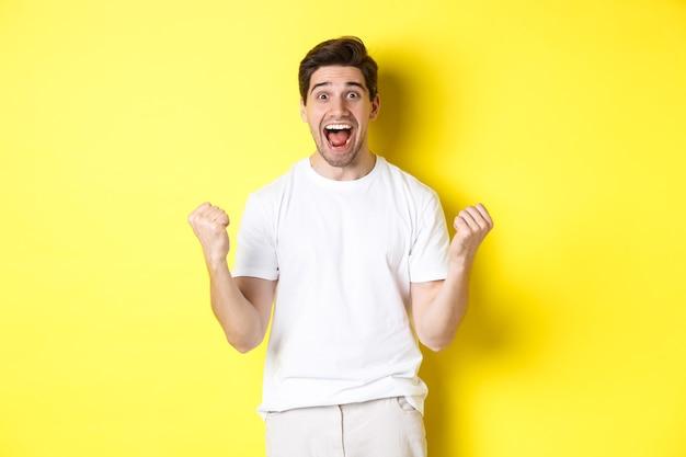 興奮して幸運な男が勝ち、拳を握りしめ、幸せそうに見え、勝利し、祝い、黄色の背景の上に立っています。
