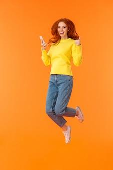 스웨터, 청바지, 오렌지 위로 점프에서 흥분과 기쁘게 잘 생긴 생강 여자