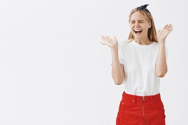 흰 벽에 포즈를 취하는 흥분되고 기뻐하는 젊은 금발 소녀