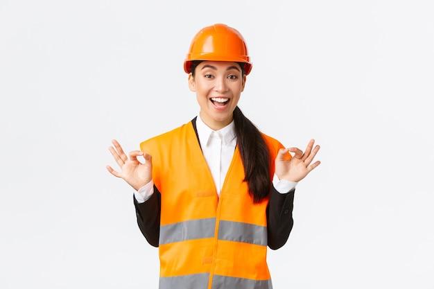 興奮して満足しているアジアの女性チーフエンジニアは、素晴らしい仕事に満足し、大丈夫なジェスチャーを示し、クライアントを保証し、完璧な品質を保証し、白い背景の上に安全ヘルメットに立っています