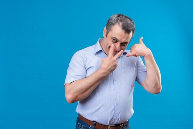 2本の指を示す青いシャツを着て興奮し、笑みを浮かべて中年の男と呼んで、青いスペースにサイン