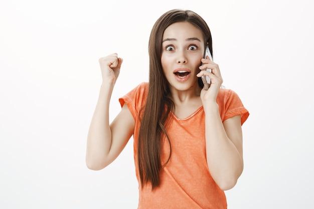 携帯電話で話し、応援し、勝利し、幸せからジャンプする興奮して驚いた魅力的な女の子
