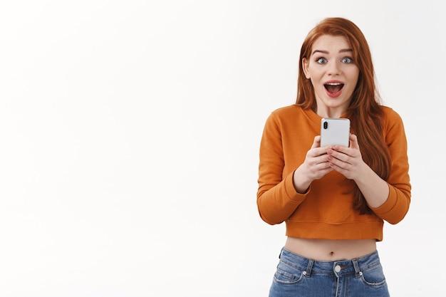 Взволнованная и удивленная, впечатленная рыжая женщина берет смартфон, чтобы записать захватывающий живой концерт, очарованный открытым ртом, подносит мобильный телефон к груди, фотографирует что-то потрясающее.