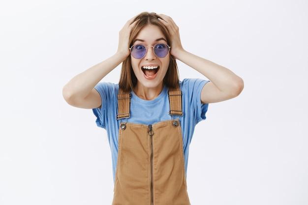 Взволнованная и удивленная красивая девушка видит потрясающее предложение, реагирует изумленно и счастливо