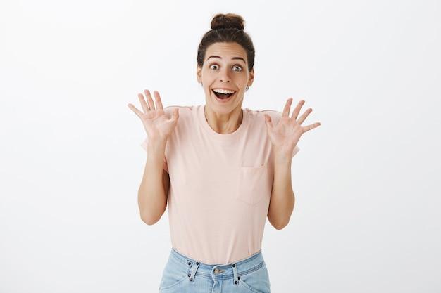Взволнованная и удивленная молодая стильная женщина позирует у белой стены