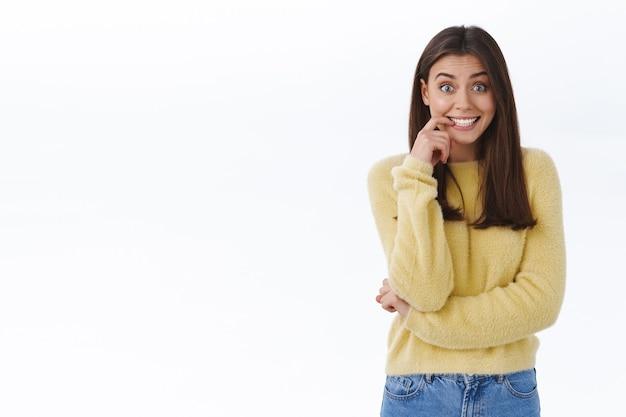 黄色いセーターを着た興奮した明るい若い女性のブルネットの女性は、興奮して圧倒され、希望に満ちたカメラを探しているように指を噛み、良いニュースを期待し、白い壁に好奇心をそそる