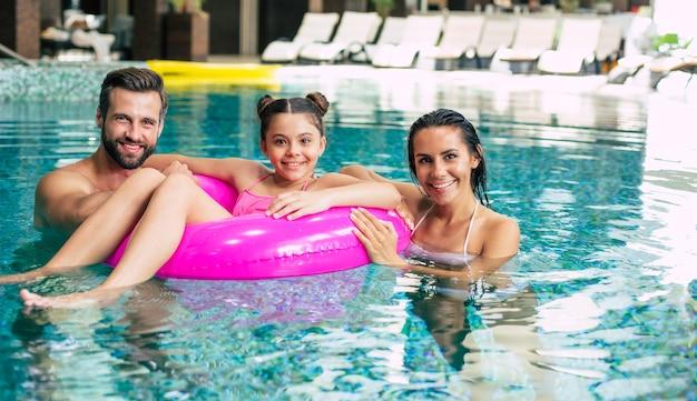 스파 호텔에서 휴가를 보내는 흥분되고 젊은 행복한 가족은 휴식을 취하고 수영장에서 즐거운 시간을 보냅니다. 여름 휴식