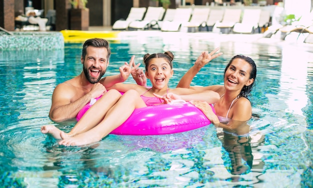 Взволнованная и молодая счастливая семья на отдыхе в спа-отеле отдыхает и веселится в бассейне. летний отдых