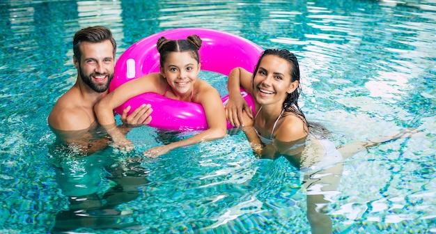 スパホテルで休暇中の興奮して若い幸せな家族はリラックスしていて、スイミングプールで楽しんでいます。夏休み