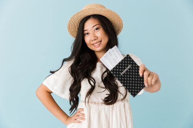 Возбужденная азиатская красивая женщина изолирована над синей стеной, держащей паспорт с билетами