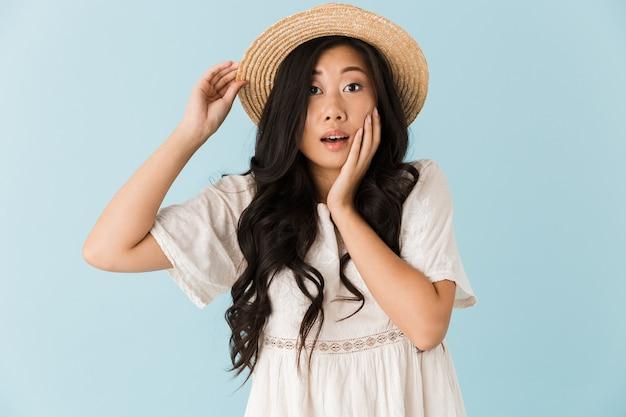 青い壁に隔離された興奮したアジアの美しい女性
