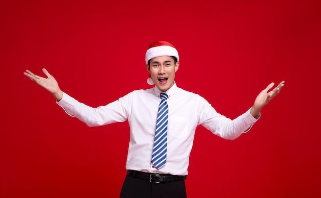 サンタの帽子と赤い壁の上の孤立したアクションオープンハンドジェスチャーを身に着けている興奮したアジアのビジネスマン。明けましておめでとうございます。