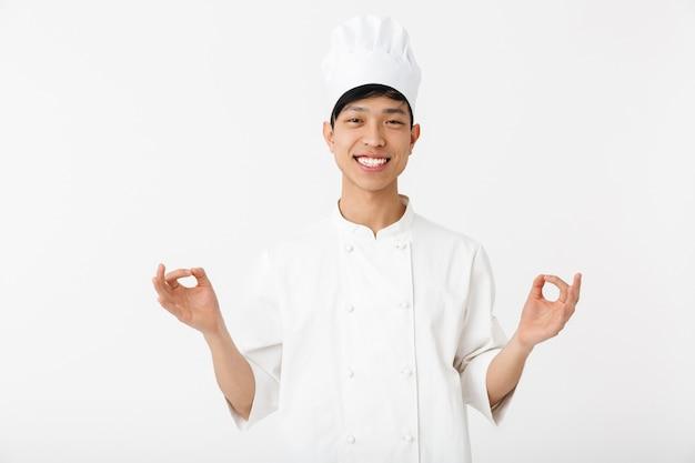 흰색 벽 위에 절연 유니폼 서 입고 흥분된 아시아 요리사, 몸짓, 확인