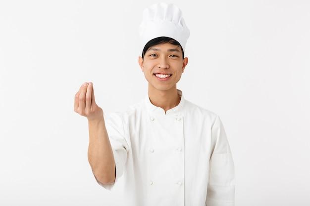 흰색 벽 위에 절연 유니폼 서 입고 흥분된 아시아 요리사 몸짓