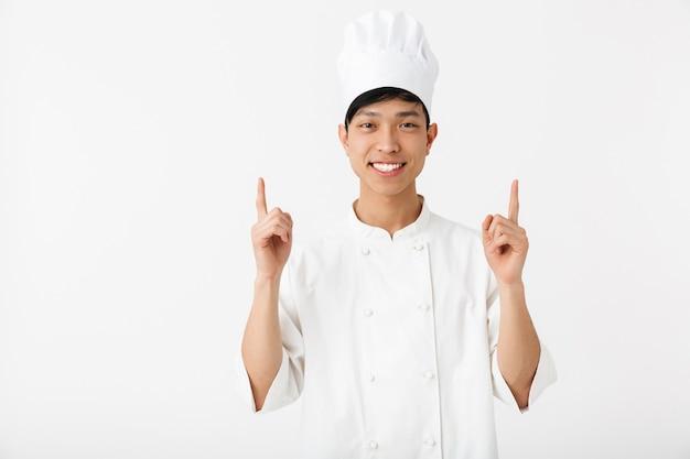 Взволнованный азиатский шеф-повар в униформе стоит изолированно над белой стеной, указывая на копировальное пространство