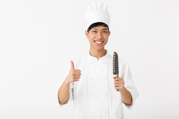 Взволнованный азиатский шеф-повар в униформе стоит изолированно над белой стеной и показывает кухонное оборудование