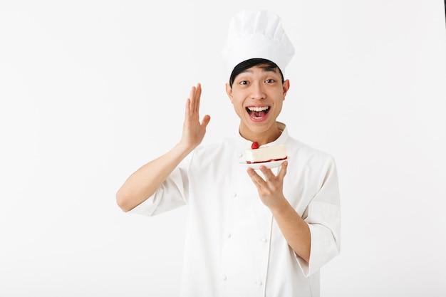 접시에 케이크 조각을 보여주는 흰 벽 위에 절연 유니폼 서 입고 흥분된 아시아 요리사