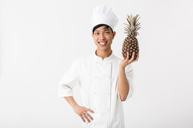 파인애플을 보여주는 흰 벽 위에 절연 유니폼 서 입고 흥분된 아시아 요리사