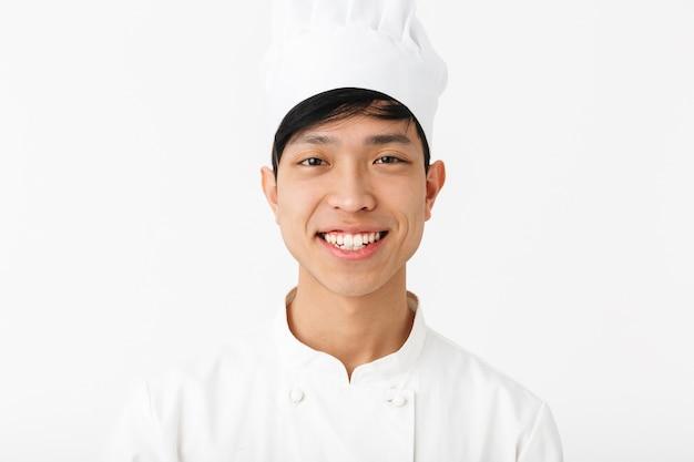 흰 벽 위에 절연 유니폼 서 입고 흥분된 아시아 요리사