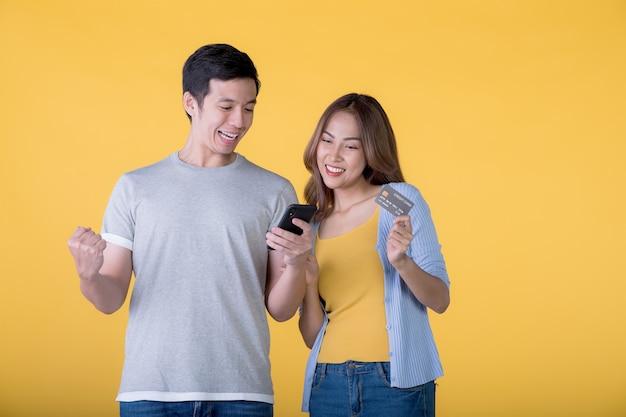 色の背景で隔離の携帯電話を見ながら興奮してクレジットカードとスマートフォンを保持している興奮したアジアのカップル Premium写真