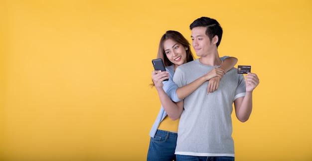 色の背景で隔離の携帯電話を見ながら興奮してクレジットカードとスマートフォンを保持している興奮したアジアのカップル