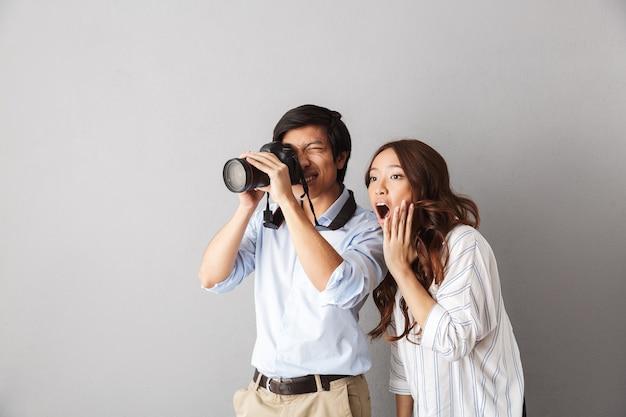 Взволнованная азиатская пара стоит изолированно, фотографируя с фотоаппаратом