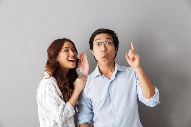 Взволнованная азиатская пара стоит изолированно, рассказывая секреты друг другу