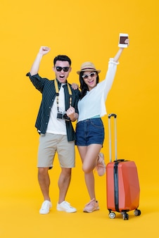 Excited asian couple tourists with luggage raising hands up and yelling