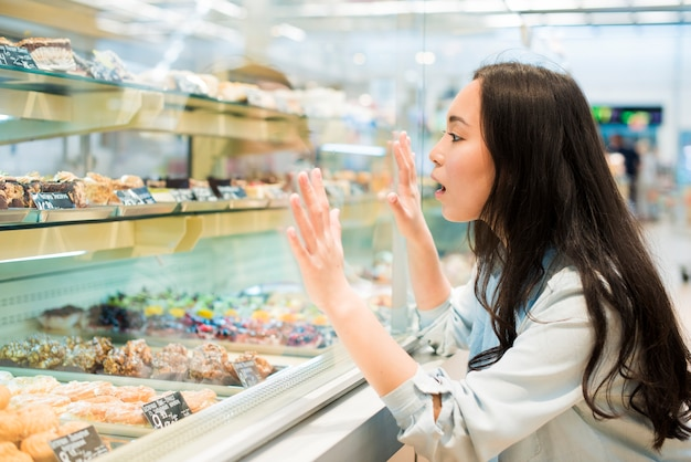 Excited asian female looking on confectionery in pastry store