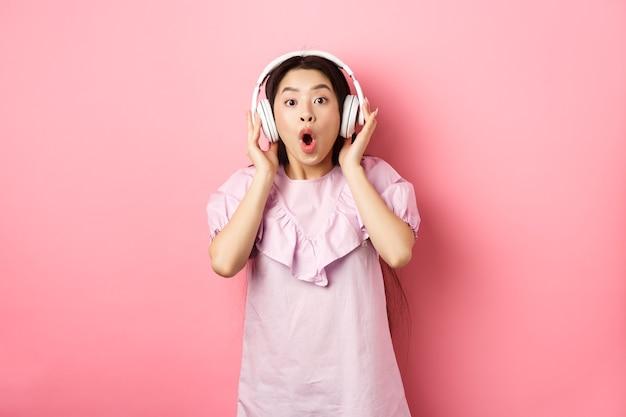 興奮したアジアの女の子は素晴らしい歌を聞いてヘッドフォンで音楽を聴き、ピンクのバックの上に立って驚いているように見えます...