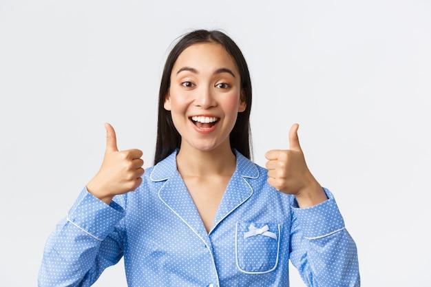 Возбужденная азиатская девушка в синей пижаме рекомендует совершенно классный товар, изумленно показывает поднятые вверх большие пальцы, нравится и соглашается, говорит хорошо или хорошо работает, хвалит хорошую работу, поддерживает стоя на белом фоне