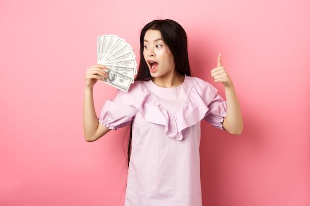 Возбужденная азиатская девушка смотрит на большие деньги и делает большие пальцы руки вверх, стоя, пораженная долларовыми купюрами на розовом фоне.
