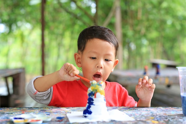 Excited asian little baby boy paint on stucco doll