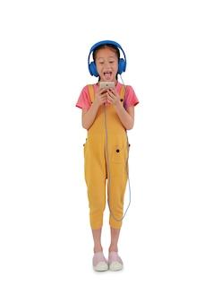 Возбужденный азиатский ребенок маленькой девочки стоит и наслаждается смартфоном и наушниками, изолированными на белом фоне. изображение с обтравочным контуром