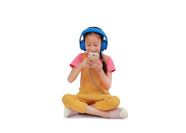 ヘッドフォンを身に着けている興奮したアジアの小さな女の子の子供と白い背景で隔離のスマートフォンに座ってお楽しみください。クリッピングパスのある画像