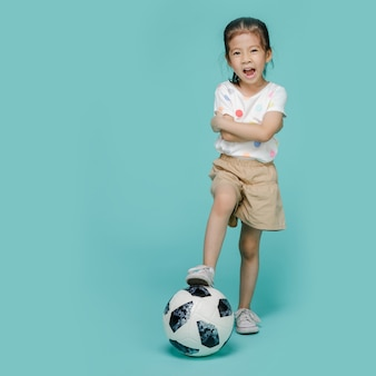 Excited asian little girl playing football, empty space isolated on colorful blue wall
