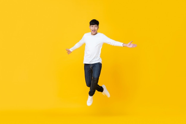 Excited asian man jumping over yellow