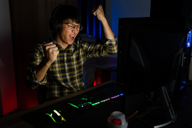 Excited asian man pro gamer sitting at the table, playing and winning in online video games on a computer and smartphone, technology gaming cyber or e-sport championship concept.