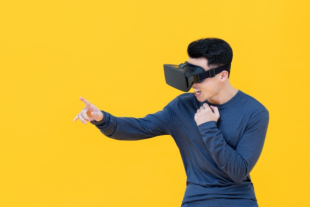 Excited asian man reaching hand out touching somthing while watching  3d simulation video from virtual reality or vr glasses on yellow wall