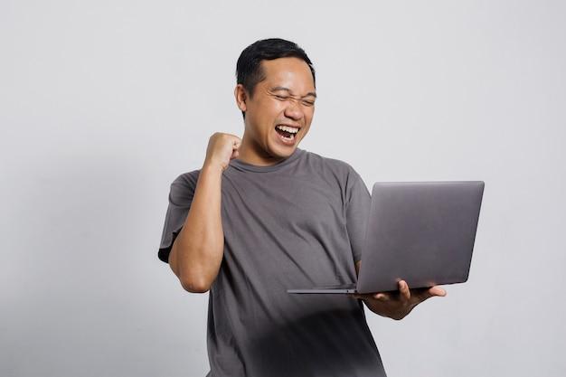 ラップトップを探している勝利のジェスチャーで興奮したアジア人