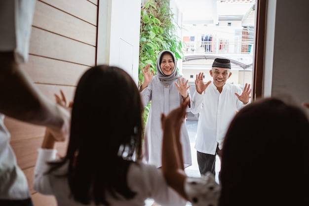Excited asian muslim grandparents visiting their grandchildren at home