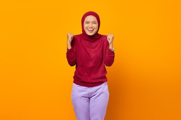 先を見据えて笑顔で勝利を祝う興奮したアジアのイスラム教徒の女性