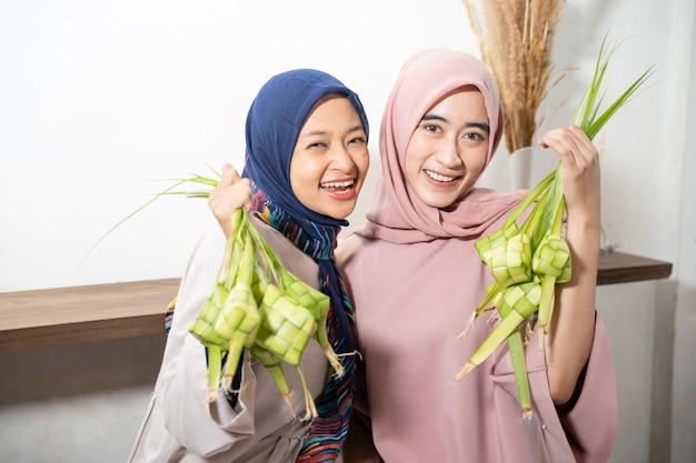 Excited asian muslim woman making ketupat rice with coconut leaf during ramadan kareem preparing for eid fitri mubarak celebration