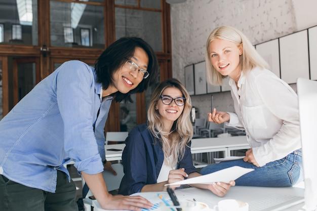 Studente asiatico emozionante in camicia blu che prepara per gli esami con la ragazza femminile caucasica in vetri