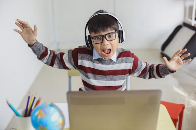 ノートパソコンを探して良いニュースを得る興奮したアジアの学生