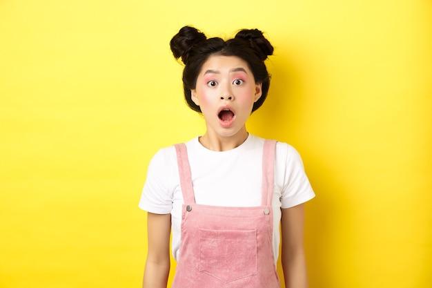 흥분된 아시아 십 대 소녀 드롭 턱, 열린 입으로 놀란 헐떡이며 카메라를보고 감동하고, 여름 프로모션 제안을 확인하고, 노란색에 서 있습니다.