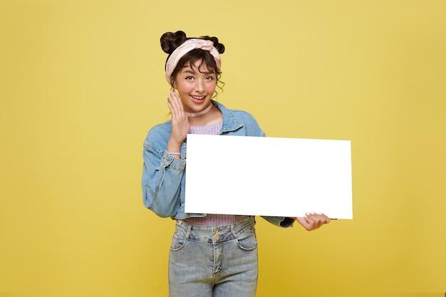 黄色の壁に空白の吹き出しを保持している興奮したアジアの 10 代の少女。